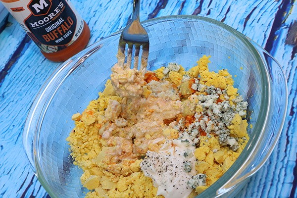 mixing yolks with buffalo sauce and blue cheese for deviled eggs recipe