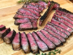 sliced T-bone steak on board