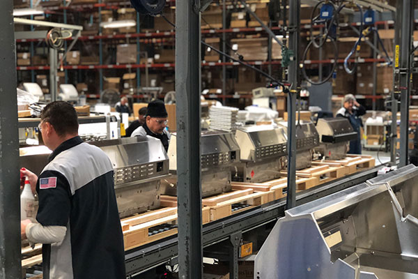 factory workers test firing burners at lynx grills factory