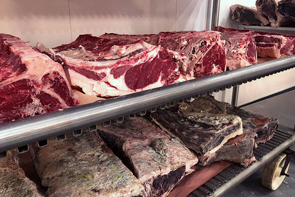 beef dry aging on racks at seven hills processing plant