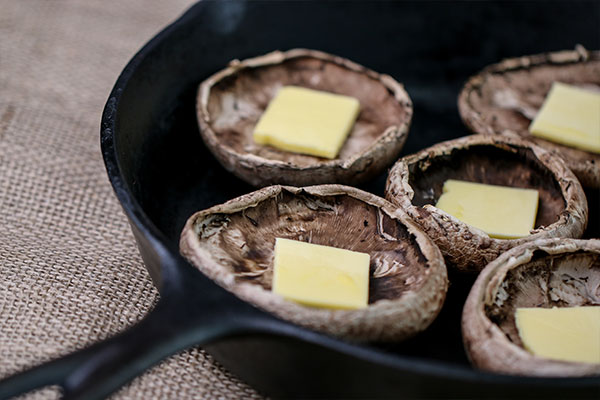 portobello mushroom with butter in cast iron pan for crab stuffed mushroom recipe