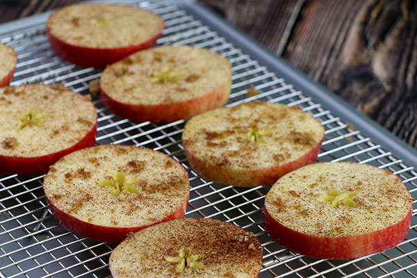 Apple slices coated in butter and sprinkled with cinnamon and sugar