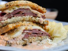 Sliced Reuben sandwich, ready to eat and served with chips