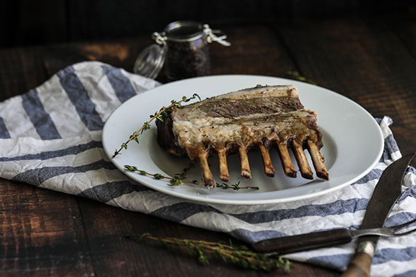 Rotisserie Rosemary Crusted Lamb on a platter ready for serving