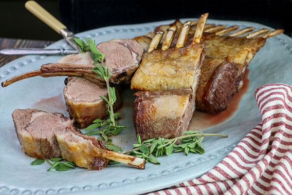 Rotisserie Rosemary Crusted Lamb sliced and served on a platter