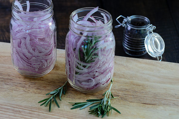 Pickled Red Onion Recipe: Thinly sliced red onions in a jar with or without rosemary, ready for pickling