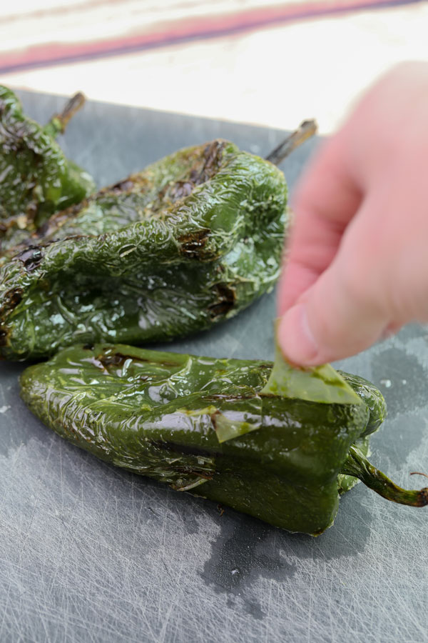 pulling the skins off of charred poblano peppers