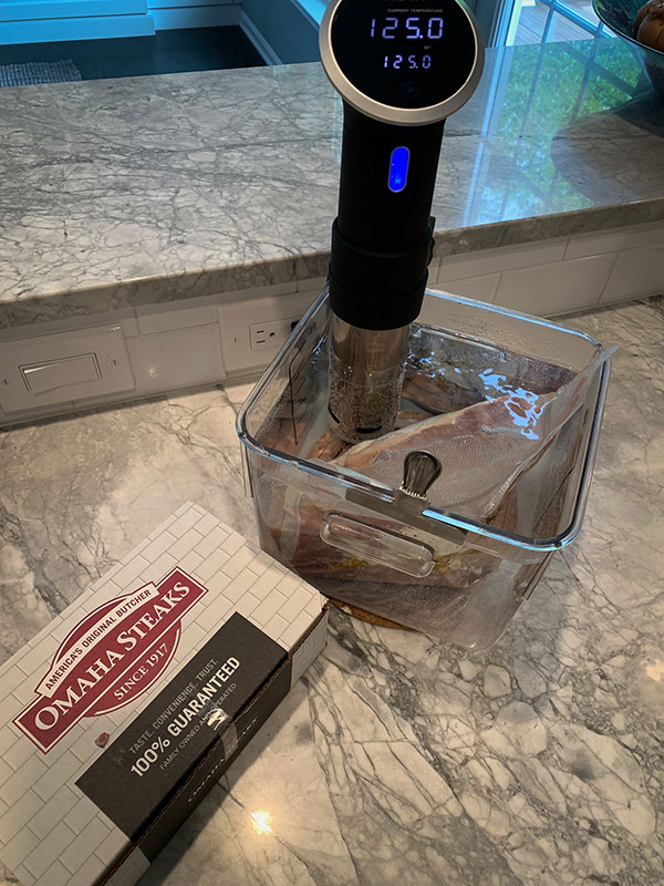 Sous vide NY strip steak in water bath cooking