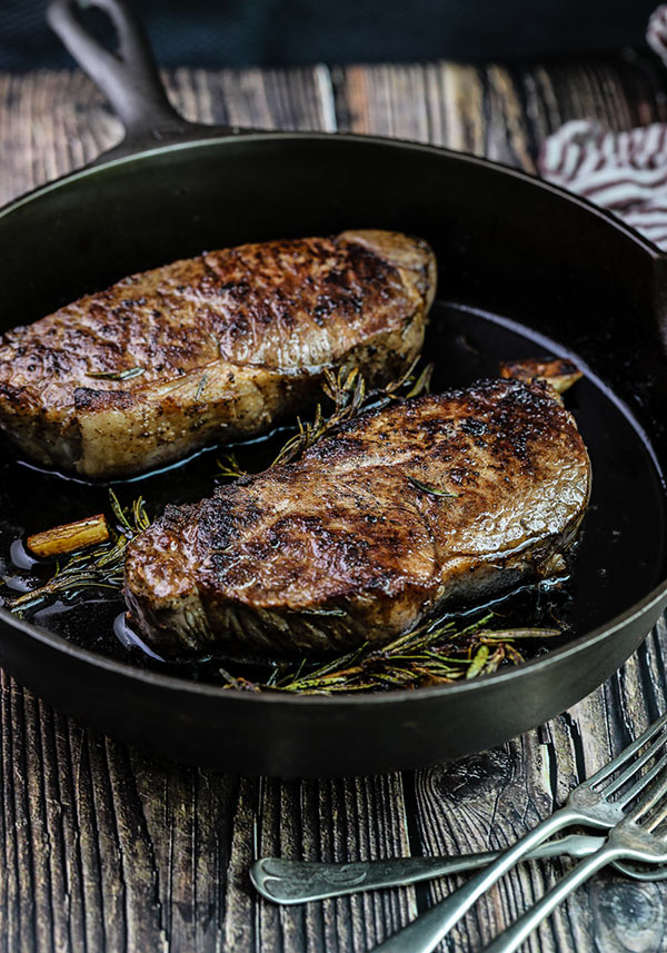 New York Strip Steaks seared in a cast iron pan