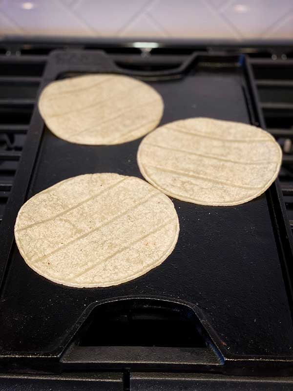 corn tortilla warming on the griddle