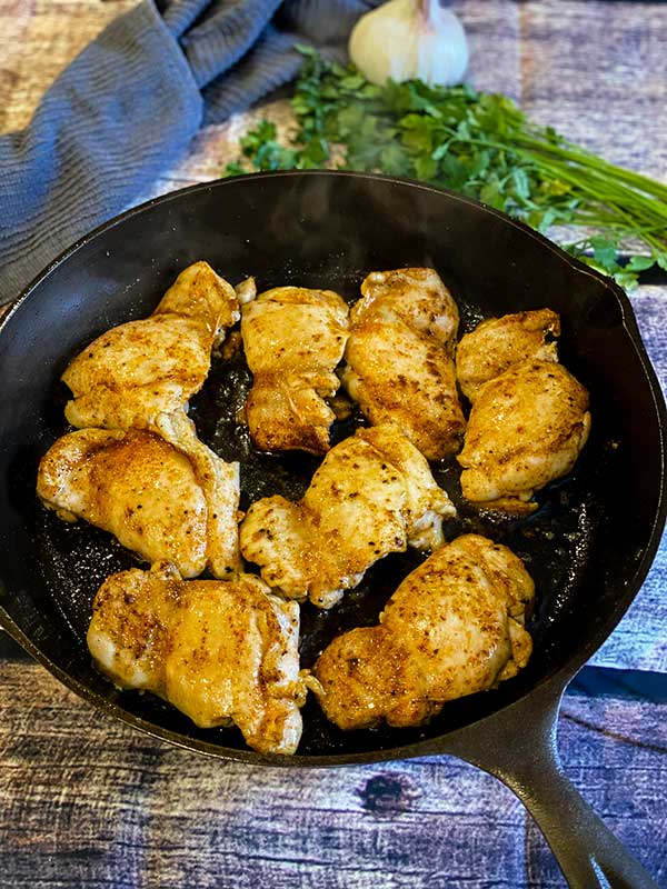 Cooked Chicken thighs in a cast iron skillet