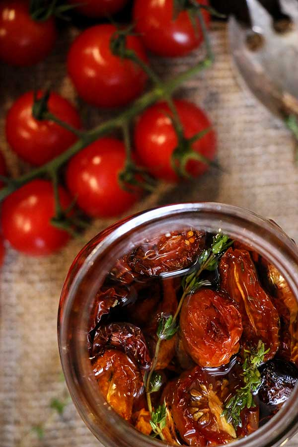 Roasted tomatoes are placed in a glass jar or freezer bag and covered with olive oil.