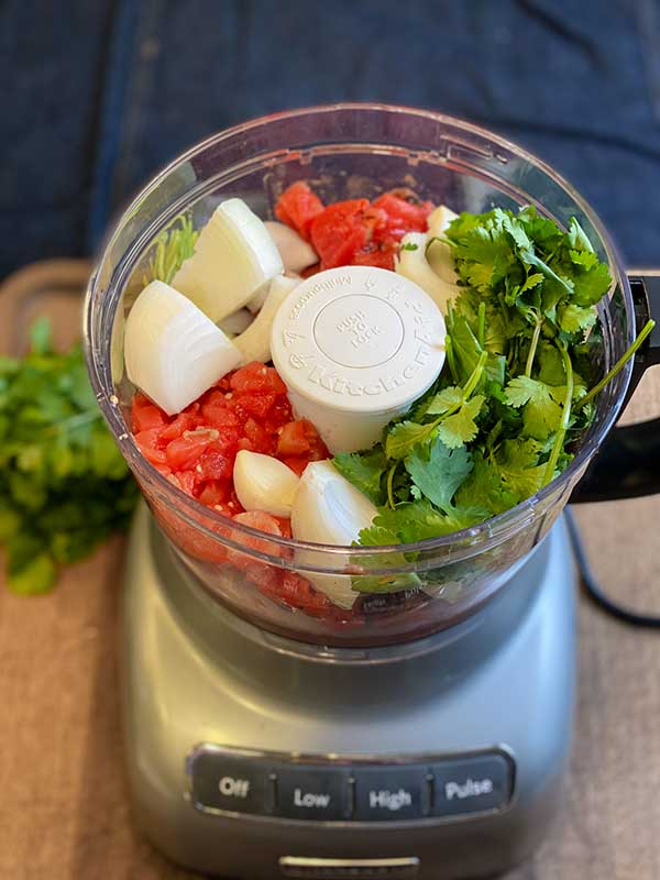 Ingredients for the restaurant style salsa in a food processor ready to be processed: chicken bouillon, garlic, onion, lime, cilantro, salt, and canned tomatoes.