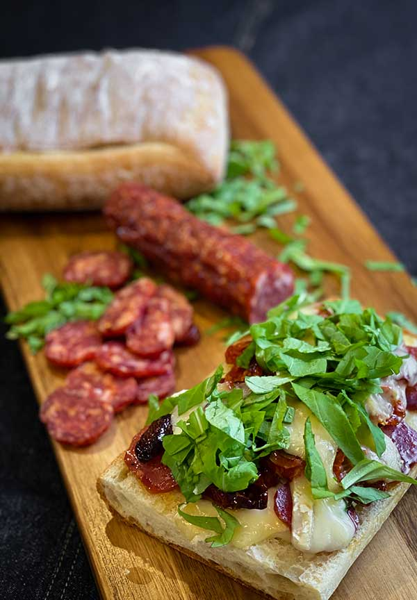 Chopped arugula, roasted tomatoes, spicy salami, and melted brie on ciabatta