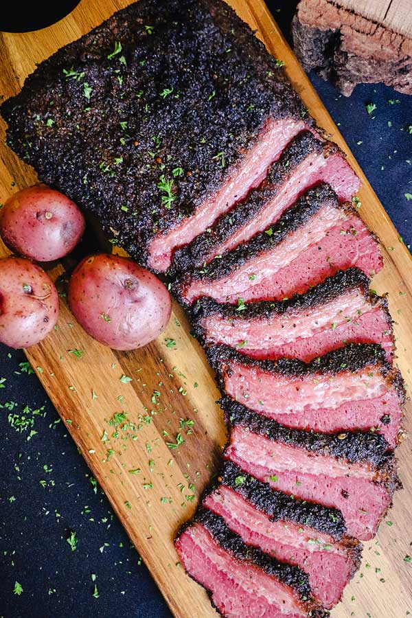 Smoked and beer braised corned beef, sliced on a cutting board with red potatoes