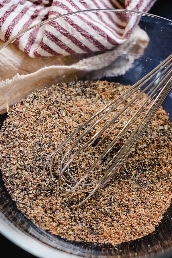 Glass bowl of spices for corned beef rub being whisked together