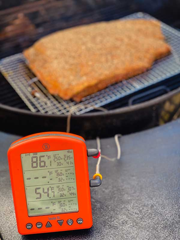 Red multi-channel Smoker X4 thermometer set up to measure temperature of grill and corned beef in background