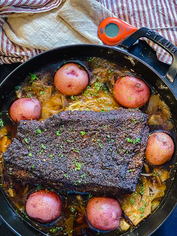 Corned beef brisket smoked and braised in beer with potatoes and cabbage using an oven safe pan