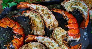 Grilled lobster tail halves plated with view of the seared lobster flesh that makes this method tasty and the shells that hold the sauce while grilling