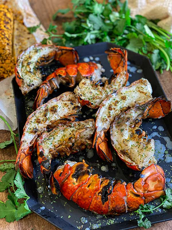 Grilled lobster tail halves plated with view of the seared lobster flesh and chipotle butter