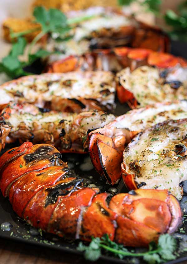 Grilled lobster tail halves with closeup of the seared lobster flesh that makes this method tasty
