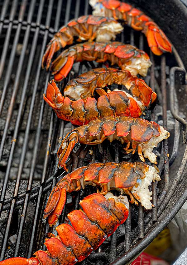 Lobster tail halves grilling meat side facing direct high heat