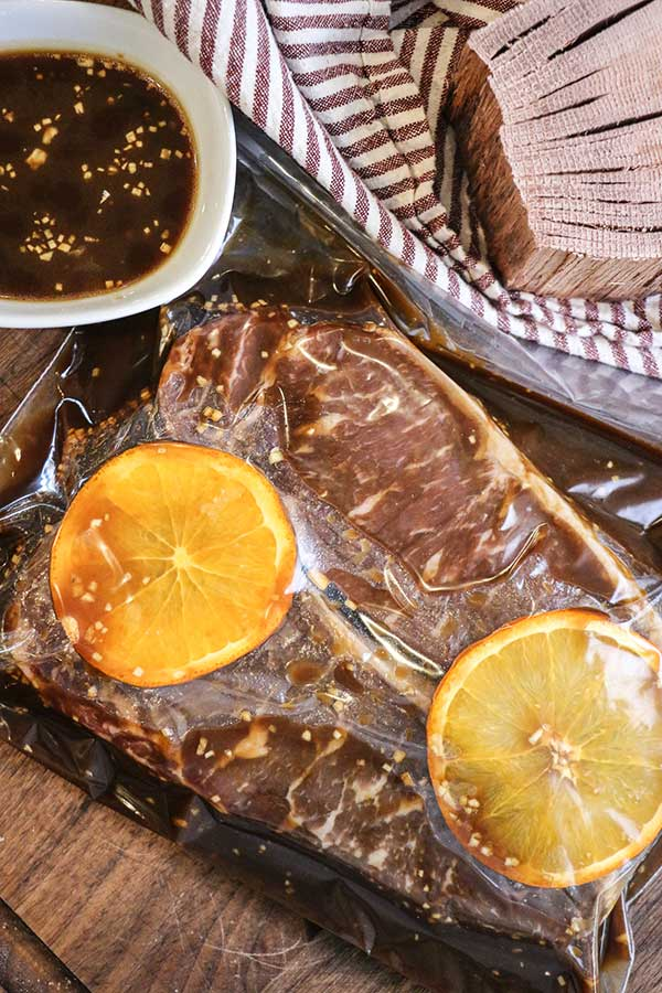 Strip steaks marinating in a bag with orange slices and bourbon marinade