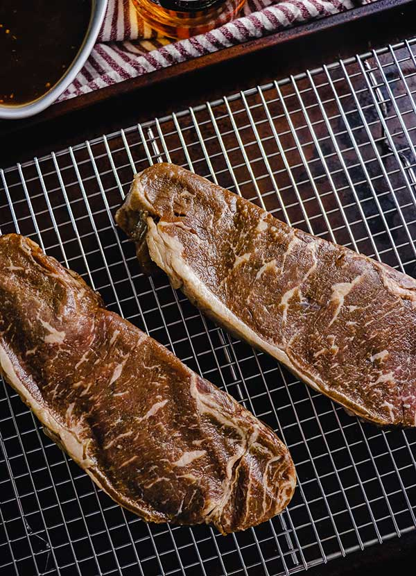 Bourbon marinated strip steak on a rack, patted dry