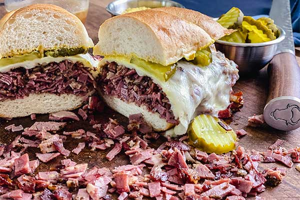 French dip pastrami sandwich on a cutting board