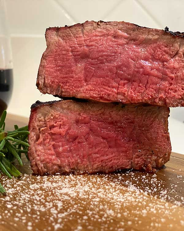 reverse seared steak with a perfect level of doneness on a cutting board
