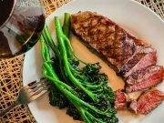 Grilled broccolini on a plate with steak
