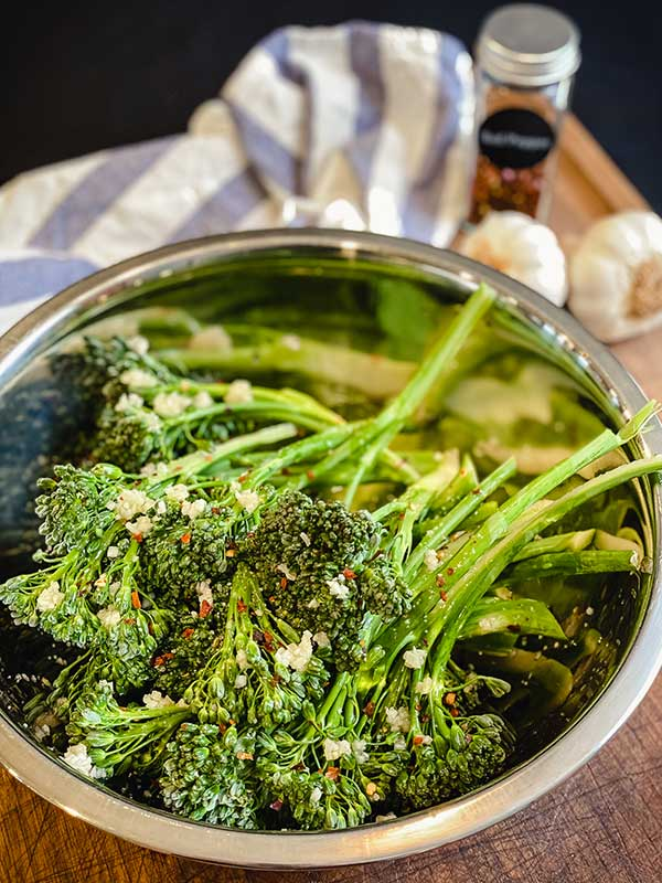 broccolini stalks in a bowl with minced garlic and olive oil