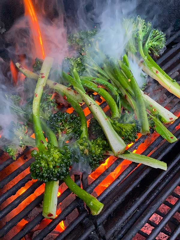 broccolini stalks on a red hot grill