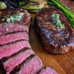 perfectly grilled New York strip steak sliced and ready to serve, on a cutting board with bok choy