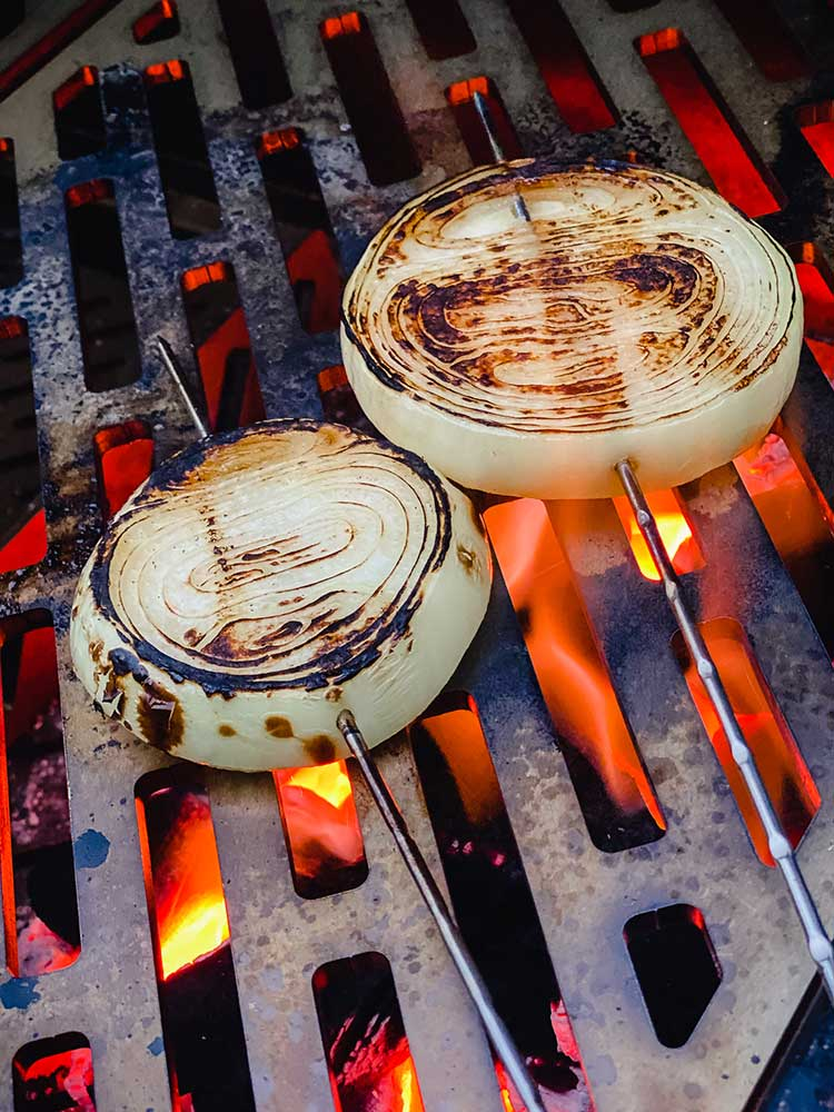 skewered onions on a high flame grill
