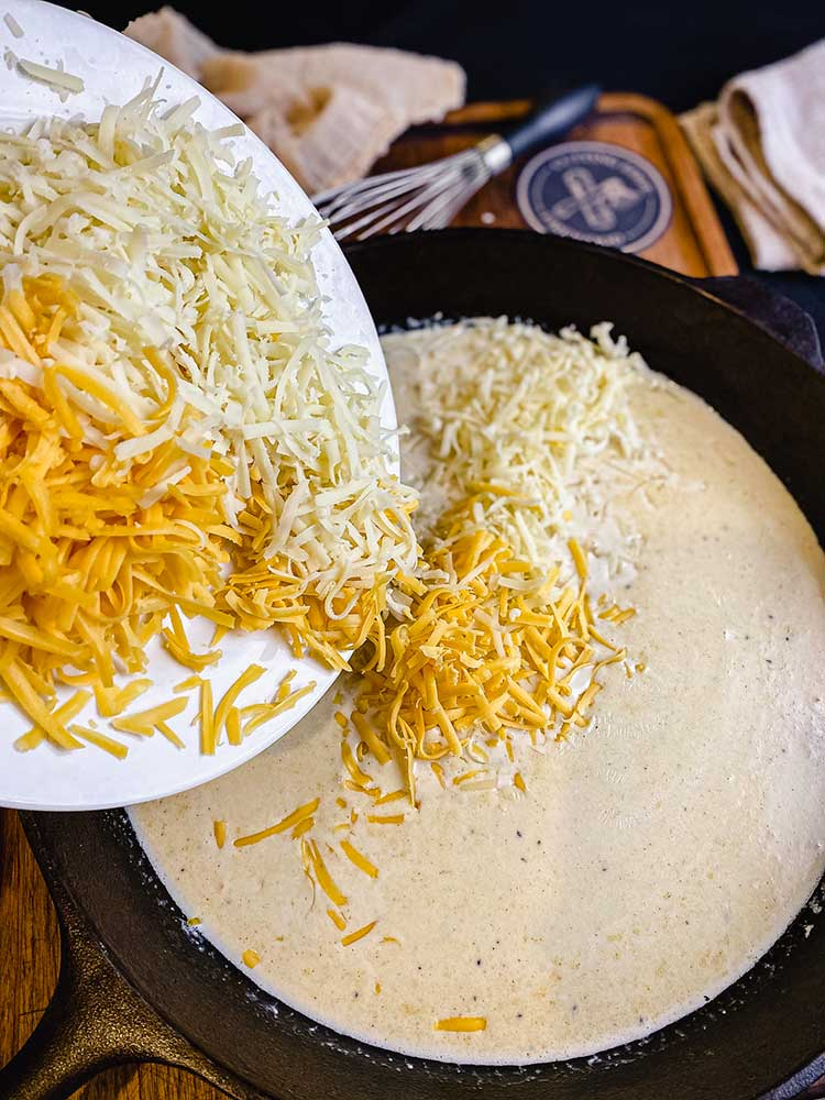 adding shredded cheeses to roux