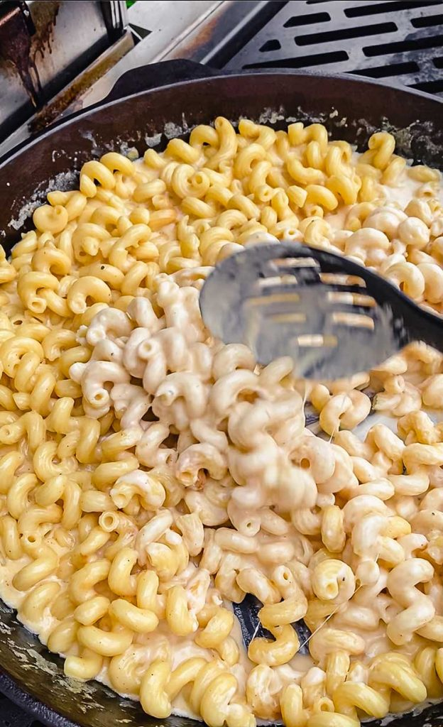 stirring pasta and cheese sauce in cast iron skillet on grill