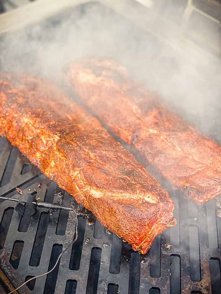 mop sauce causing steam around BBQ ribs on a grill