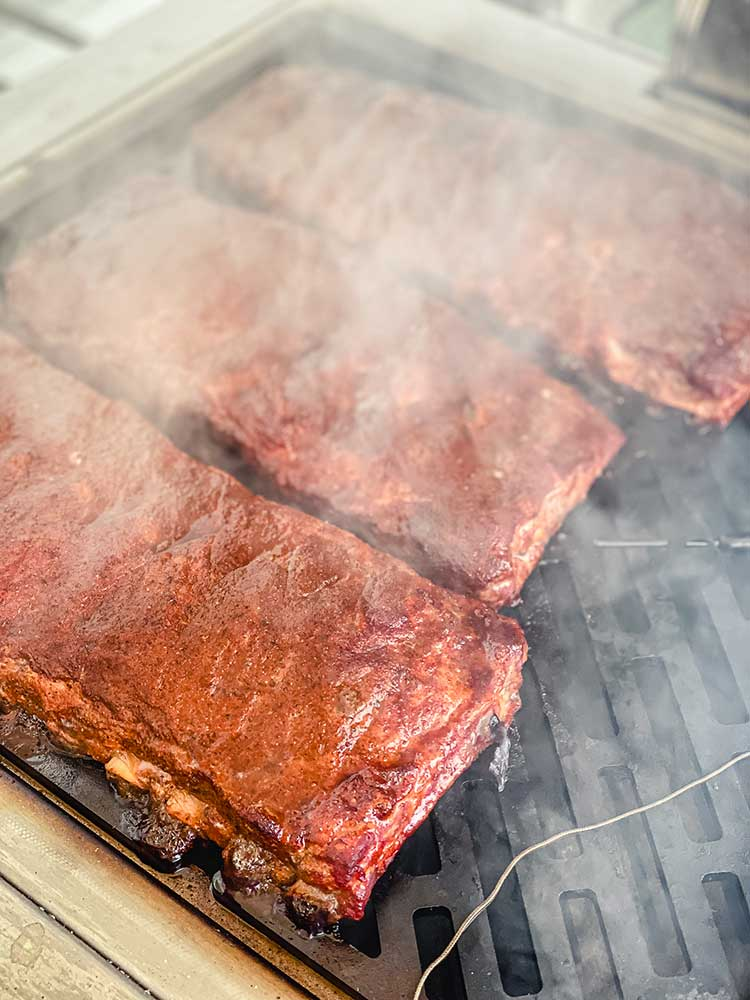 Smoking ribs on the grill with hickory and apple wood chunks of woo
