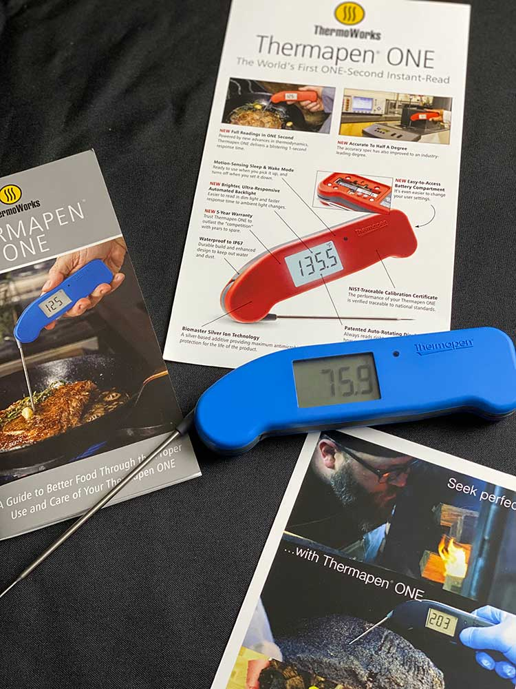 the Thermapen One displayed with its manual and features list.