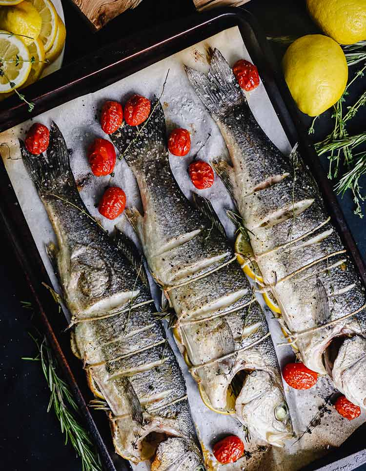 fire roasted whole branzino on a pan with roasted cherry tomatoes