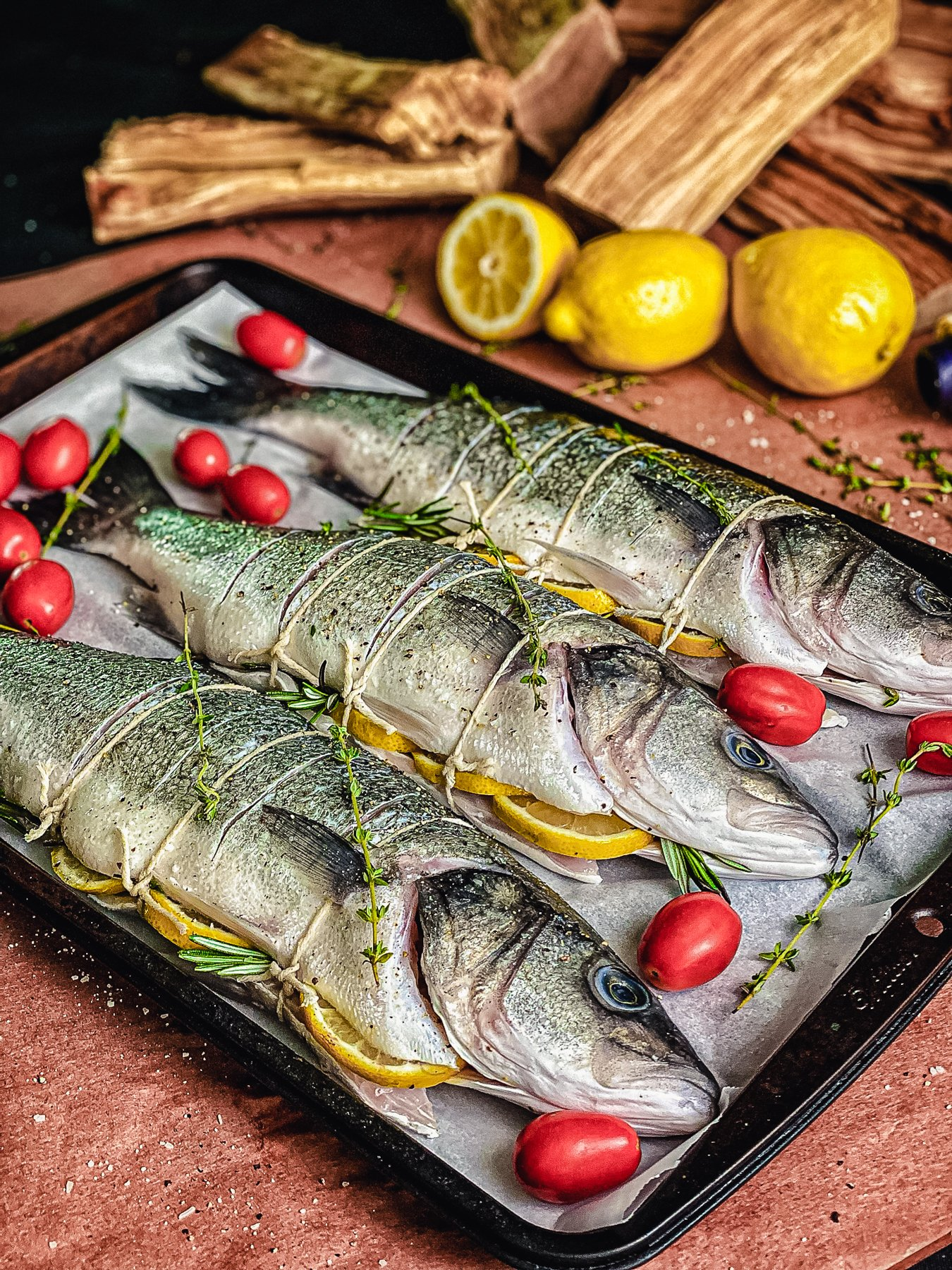 three fish and cherry tomatoes on sheet pan lined with parchment paper, ready to grill