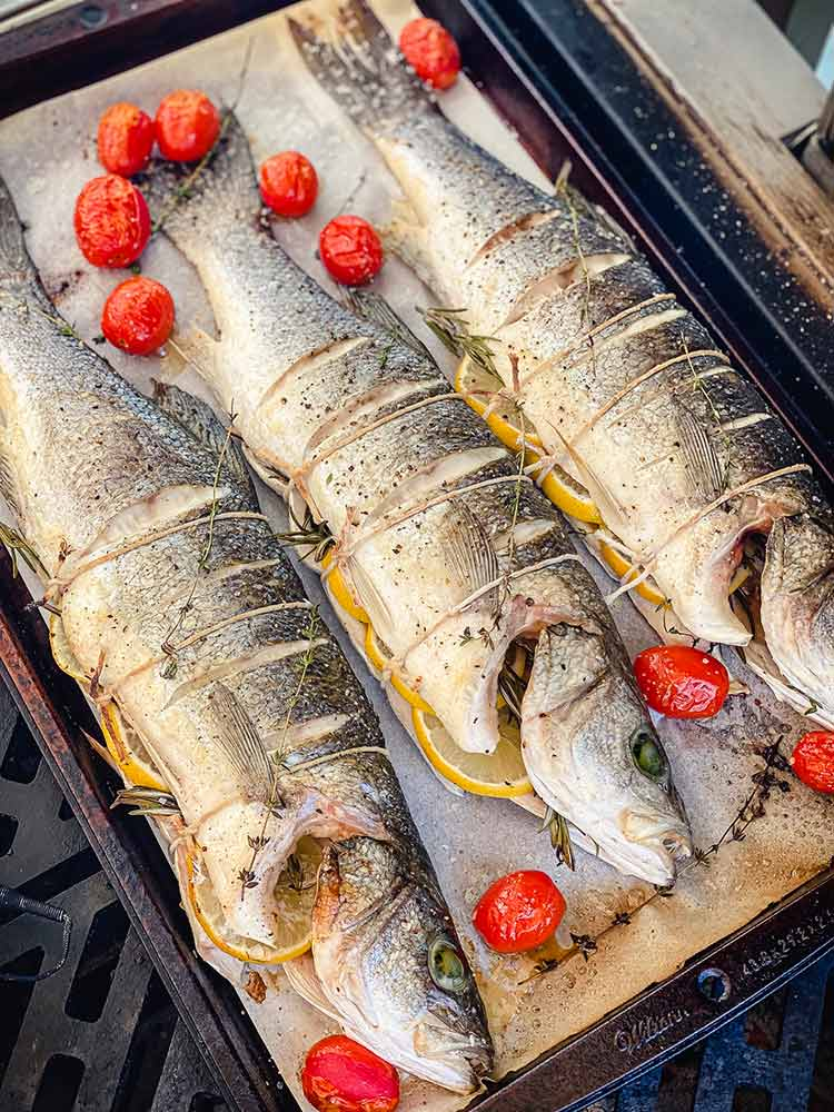 partially cooked fish and tomatoes rest in a sheet pan while grill is stoked to higher temperature