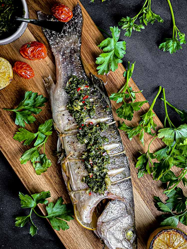 fire roasted branzino on a wood plank with roasted tomatoes, lemons and chimichurri