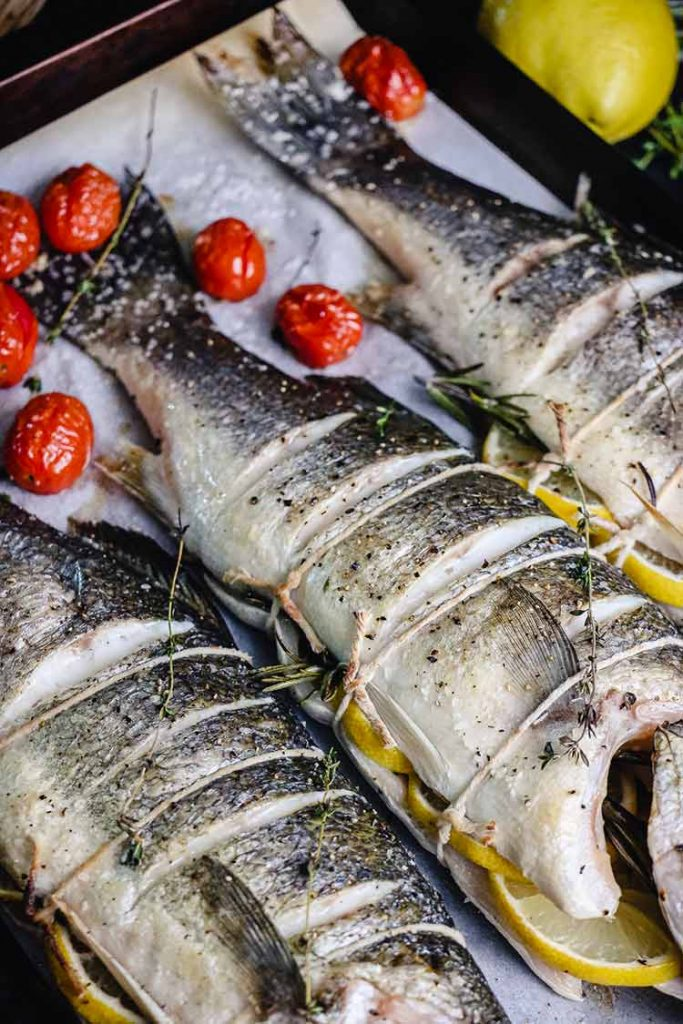 Fire roasted whole branzino, stuffed with lemon and rosemary and tied closed with twine.