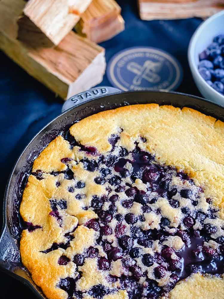 blueberries bubble through the crust of smoked cobbler