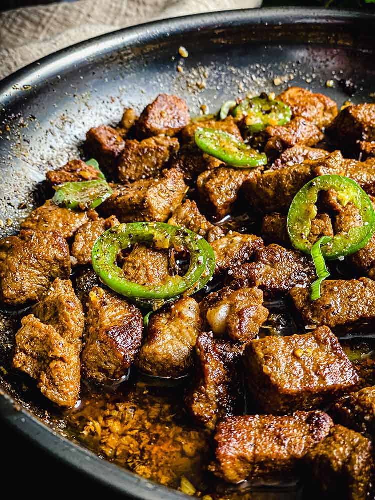 steak with sliced jalepeno and minced garlic, close up