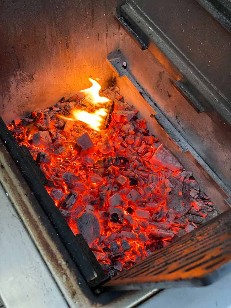 grill with chunks of oak firewood and charcoal